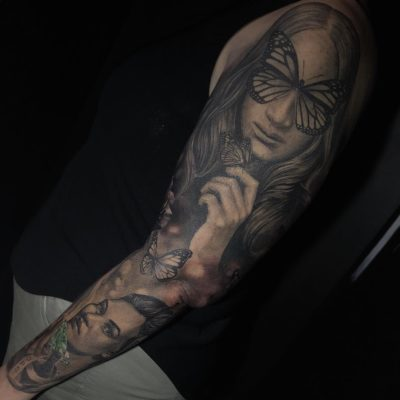 Sleeve tattoo in black and grey realism with portraits