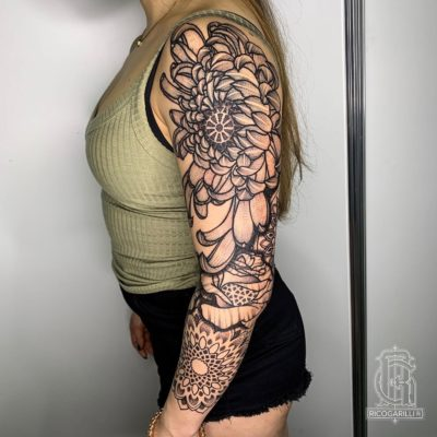 Sleeve tattoo of floral and mandala designs by Rico Garilli